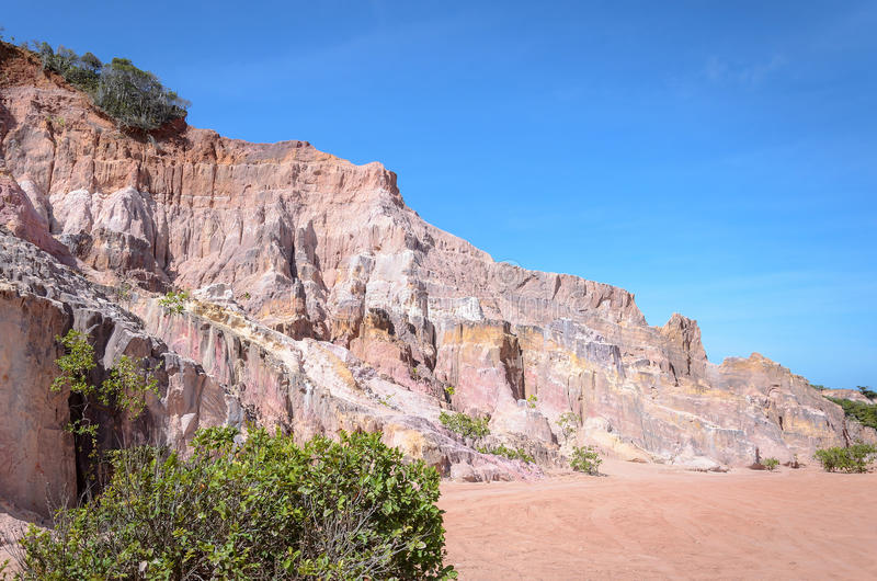 Canyon cliffs with many rocks sedimented by time, rocks with red and yellow colors. Cliffs of Coqueirinho beach, PB - Brazil royalty free stock image