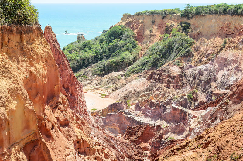 Canyon of cliffs with many stones sedimented by time, rocks with red and yellow colors and the sea in the background. Cliffs of Coqueirinho beach, PB - Brazil royalty free stock photography