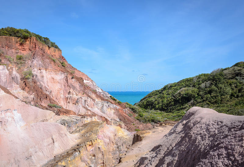 Canyon of cliffs with many stones sedimented by time. Rocks with red and yellow colors and the sea in the background. Cliffs of Coqueirinho beach, PB - Brazil royalty free stock photography
