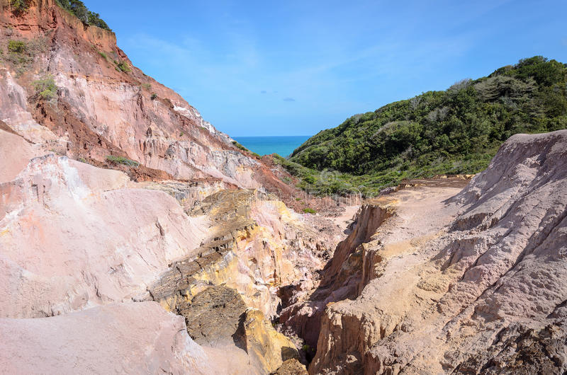 Canyon of cliffs with many stones sedimented by time. Rocks with red and yellow colors and the sea in the background. Cliffs of Coqueirinho beach, PB - Brazil royalty free stock photos
