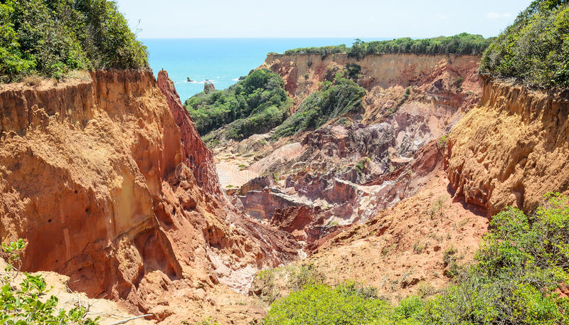 Canyon of cliffs with many stones sedimented by time. Rocks with red and yellow colors and the sea in the background. Cliffs of Coqueirinho beach, PB - Brazil stock photo