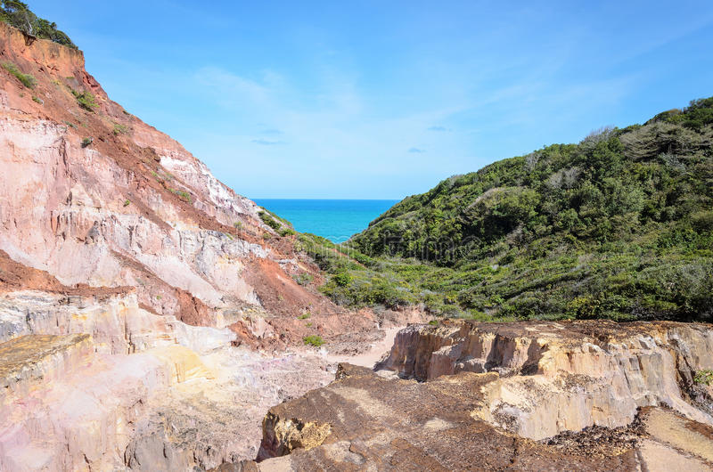 Canyon of cliffs with many stones sedimented by time. Rocks with red and yellow colors and the sea in the background. Cliffs of Coqueirinho beach, PB - Brazil royalty free stock photo