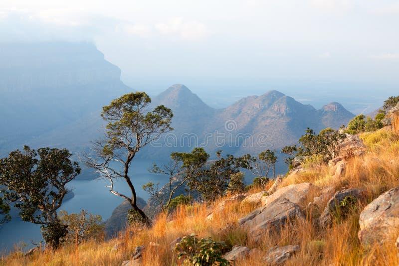 Canyon de rivière de Blyde, deux arbres verts, lac bleu et montagnes dans les nuages à l'arrière-plan de lumière de coucher du so photographie stock
