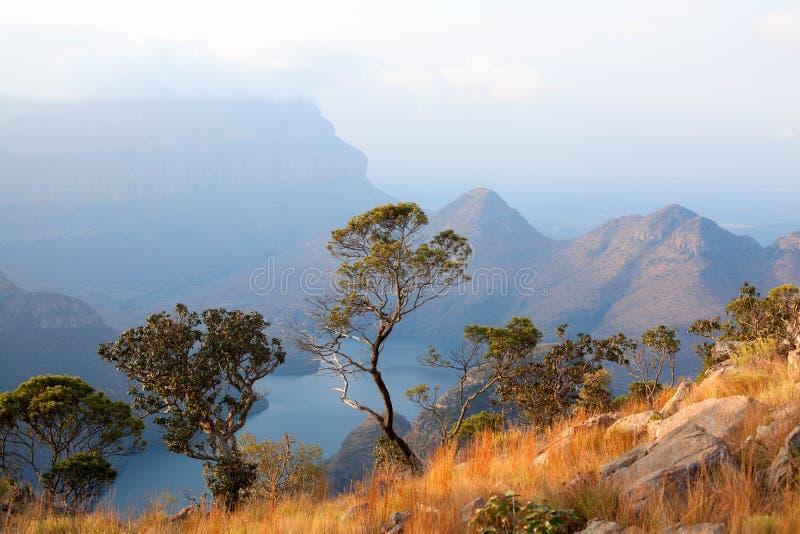 Canyon de rivière de Blyde, trois arbres verts, lac bleu et montagnes dans les nuages à l'arrière-plan de lumière de coucher du s images stock