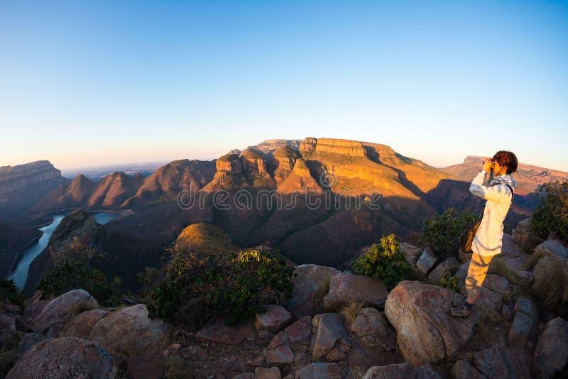 Canyon del fiume di Blyde, destinazione famosa di viaggio nel Sudafrica Turista che esamina panorama con binoculare Ultima luce s immagini stock