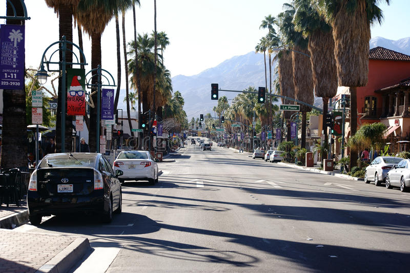Canyon Drive Palm Springs. Palm Springs, United States - December 24, 2015: Road with parked cars on the side strips and a set of traffic lights in the royalty free stock photo