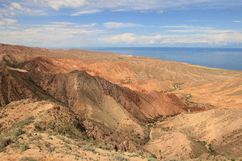 The canyon Skazka (Fairy Tale) and Issyk Kul lake on the background, Kyrgyzstan. The canyon Skazka (Fairy Tale) is located on the southern shore of Issyk-Kul stock photos