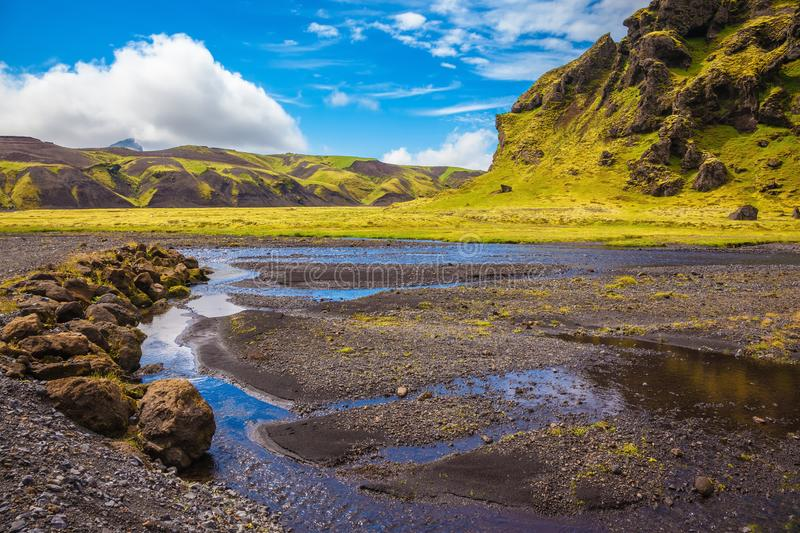 On canyon streams flow. Canyon Pakgil in Iceland. Picturesque basalt hills overgrown green grass and polar moss. On bottom of  canyon streams flow stock images