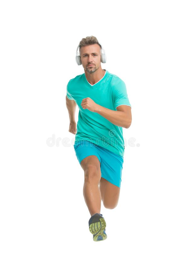 Canzone motivazionale Sportivo dell'uomo che corre con le cuffie Tipo bello del corridore forte nel moto isolato su bianco Musica fotografia stock