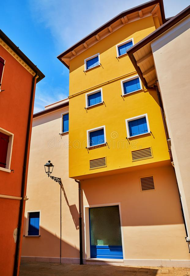 Caorle, Italy. Mediterranean resort town. Motley coloured houses. With windows and street lamp at narrow bright sunny summer day with blue sky stock images