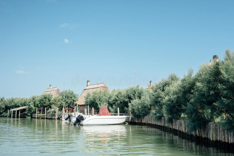 Caorle, Venice lagoon Italy. Boats moored in front of the characteristic 'casoni'. royalty free stock images