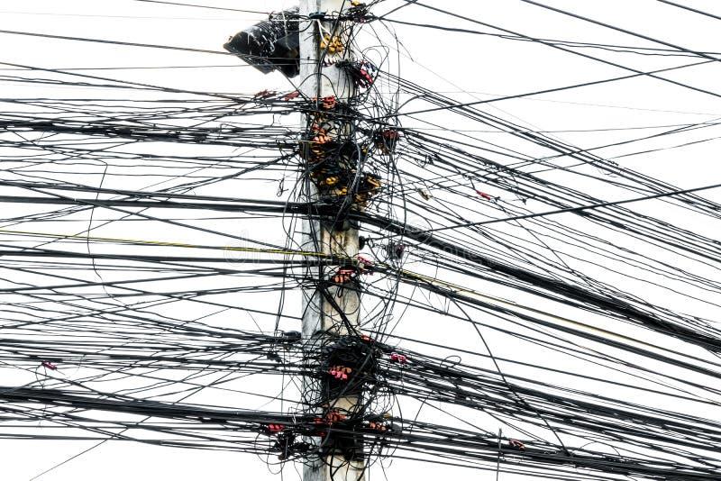 Caos desarrumado dos cabos com fios no polo elétrico no fundo branco, os muitos fio elétrico em polos de poder foto de stock royalty free