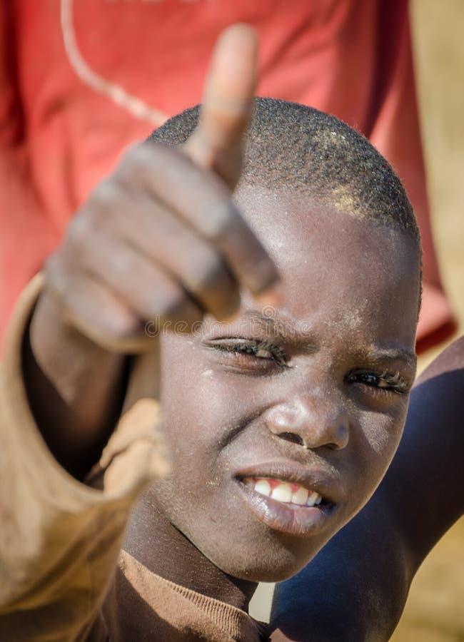 CAOTINHA, BENGUELA, ANGOLA - 11 DE MAYO DE 2014: El retrato del muchacho africano no identificado con mostrar sucio de la cara lo imagen de archivo