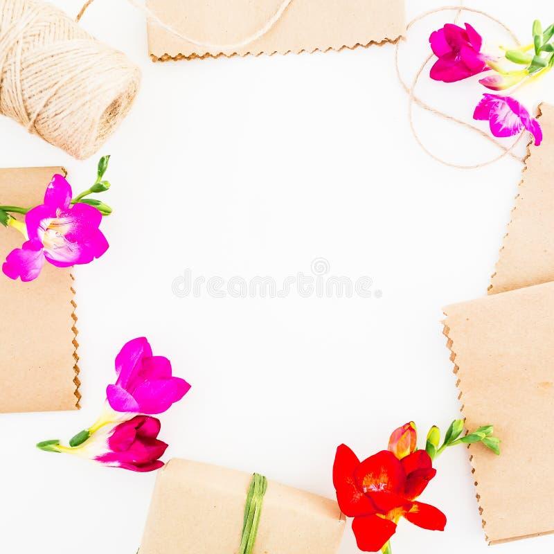 Capítulo con las flores, la caja de regalo, el documento del arte y la guita sobre el fondo blanco Endecha plana, visión superior fotografía de archivo libre de regalías