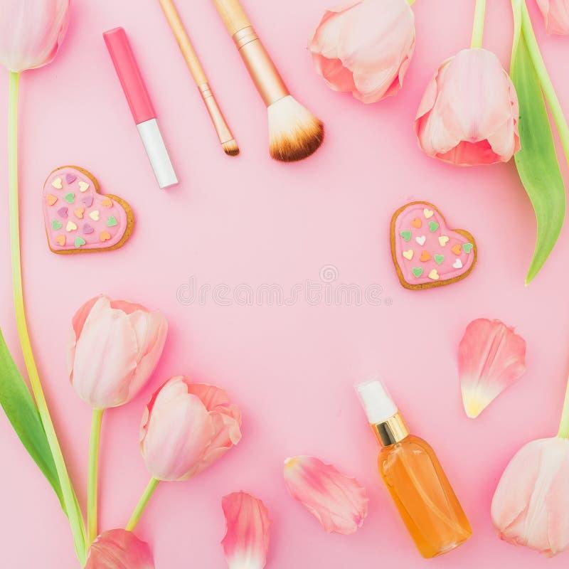 Capítulo con las flores y los cosméticos rosados, galletas de los tulipanes en fondo en colores pastel rosado Endecha plana, visi foto de archivo