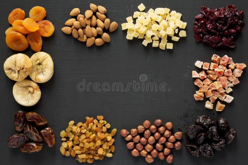 Cap?tulo de frutas y de nueces secadas en el fondo negro, visi?n superior overhead imagen de archivo libre de regalías