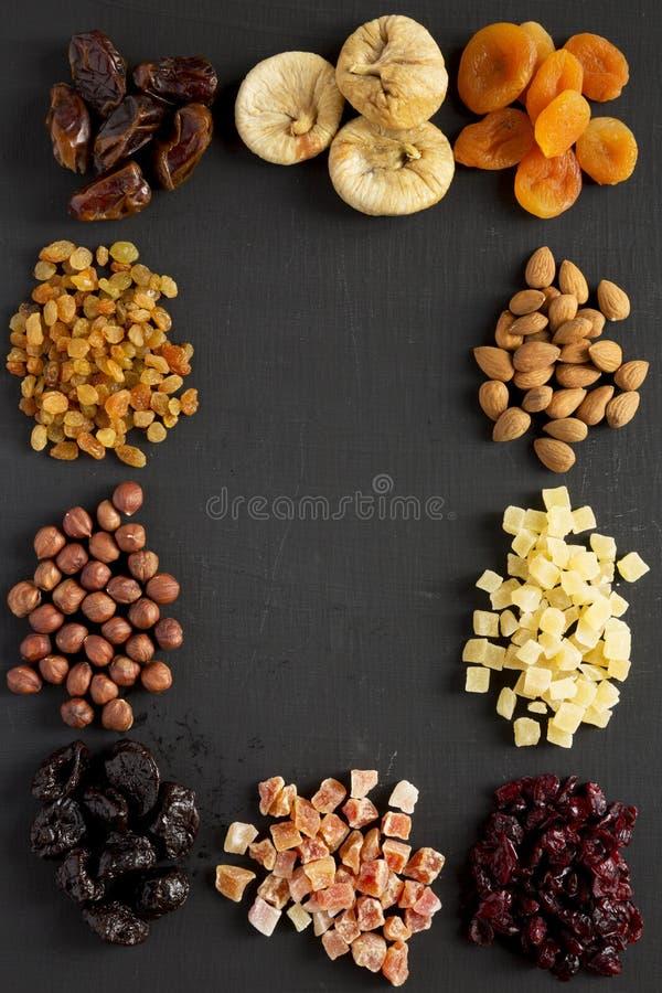 Cap?tulo de frutas y de nueces secadas en la tabla negra, visi?n superior overhead Copie el espacio imágenes de archivo libres de regalías