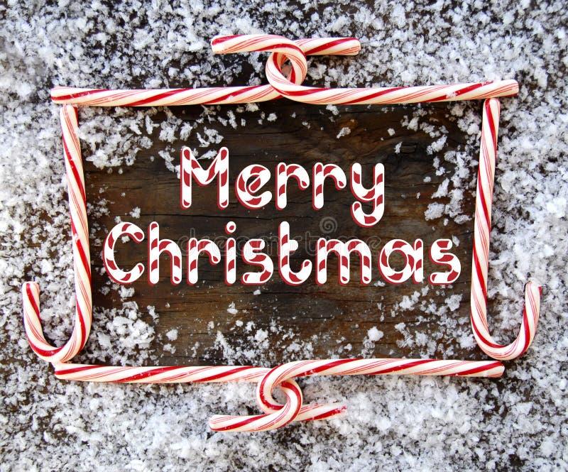 Capítulo de la Navidad del bastón de caramelo en la madera gastada imagen de archivo
