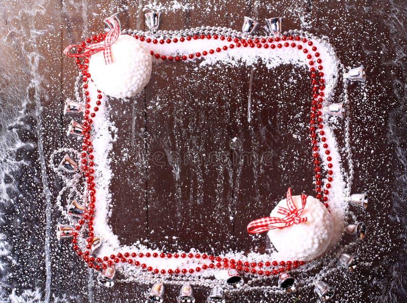 Capítulo de la nieve con las bolas de la Navidad en un folleto de madera oscuro del fondo del invierno nevoso imagenes de archivo