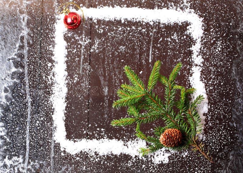 Capítulo de la nieve con un árbol de navidad y un topetón en un folleto nevoso del invierno del fondo de madera oscuro fotos de archivo libres de regalías