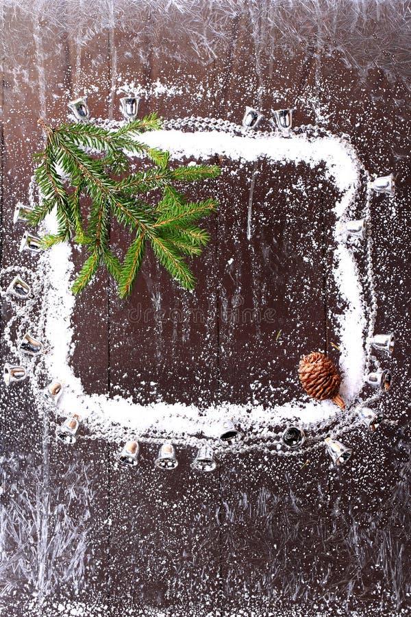 Capítulo de la nieve con un árbol de navidad y un topetón en un folleto nevoso del invierno del fondo de madera oscuro imagen de archivo