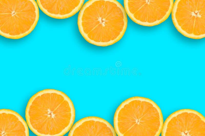 Capítulo de las rebanadas anaranjadas de una fruta cítrica en fondo azul brillante imagenes de archivo