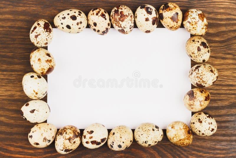 Capítulo de los huevos de codornices con la postal, fondo de madera imagen de archivo