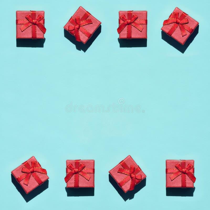 Capítulo de muchas pequeñas cajas de regalo rosadas rojas en el fondo de la textura del papel azul en colores pastel de moda del  foto de archivo