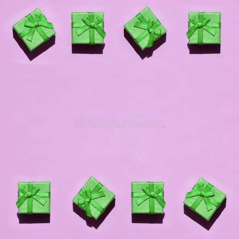 Capítulo de muchas pequeñas cajas de regalo verdes en el fondo de la textura del papel rosado en colores pastel de moda del color fotografía de archivo libre de regalías