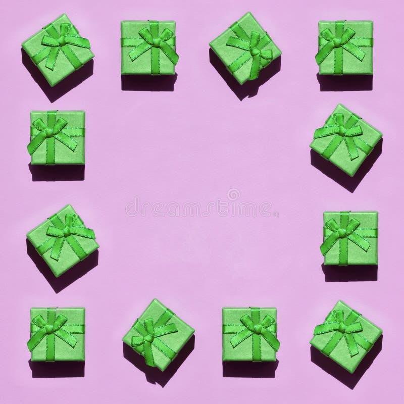 Capítulo de muchas pequeñas cajas de regalo verdes en el fondo de la textura del papel rosado en colores pastel de moda del color imágenes de archivo libres de regalías