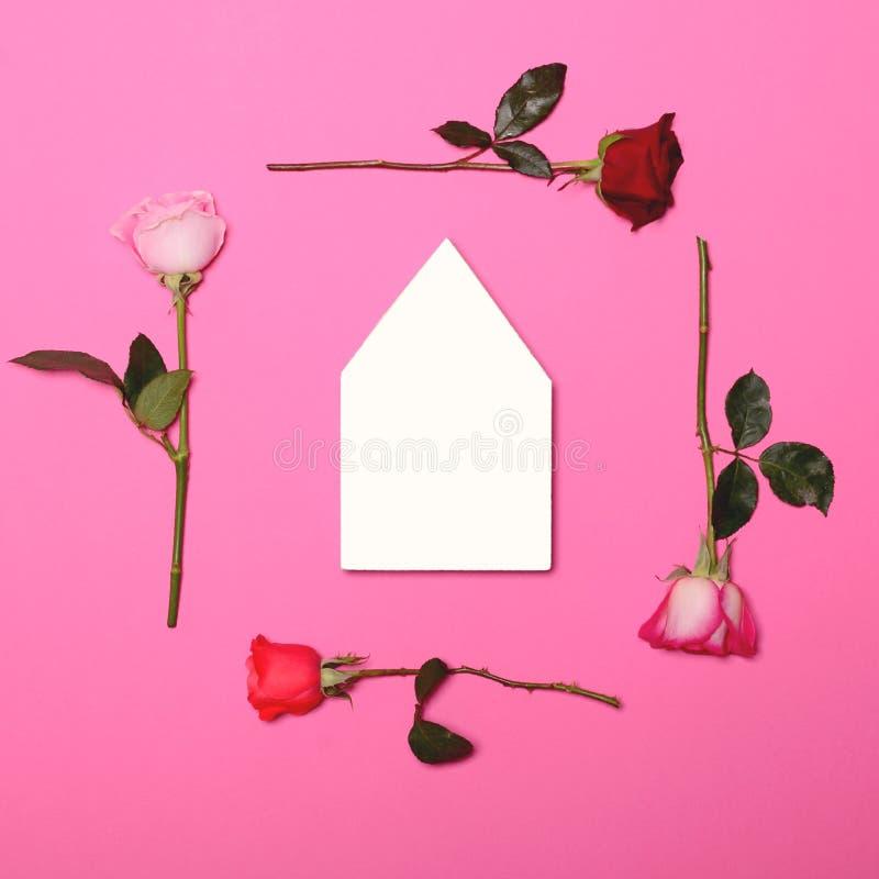 Capítulo de rosas coloridas frescas en fondo rosado en colores pastel con el tablero de madera de la forma vacía de la casa - end imagen de archivo libre de regalías