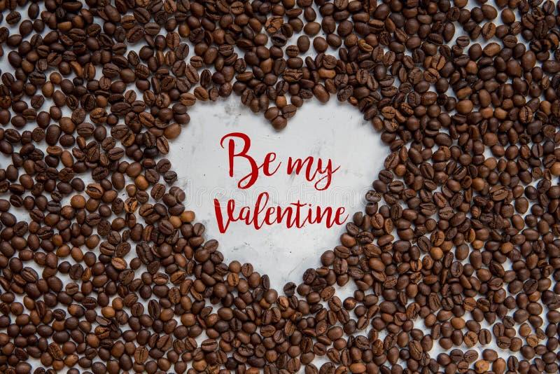 Capítulo el corazón de los granos de café con el texto - sea mi tarjeta del día de San Valentín imagen de archivo libre de regalías