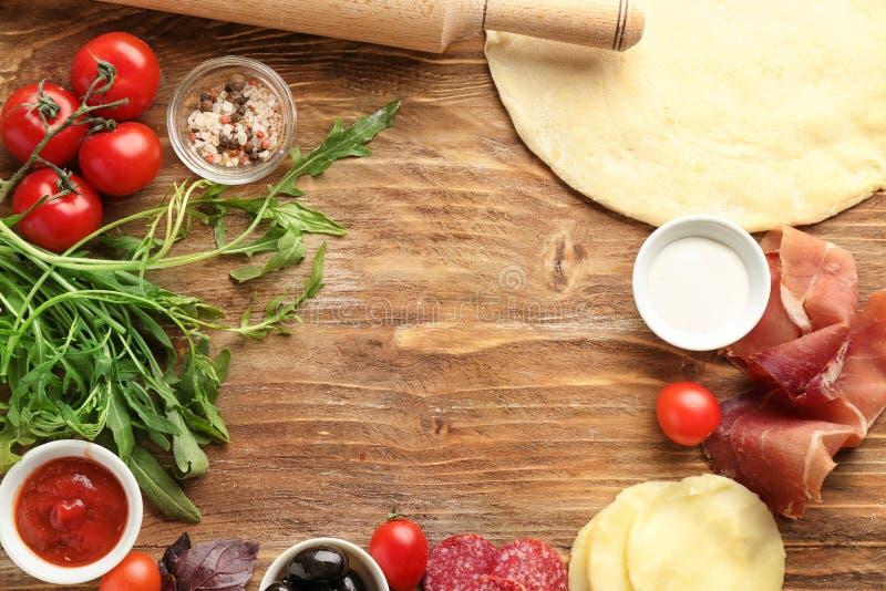Capítulo hecho con pasta e ingredientes crudos para la pizza en la tabla fotografía de archivo libre de regalías