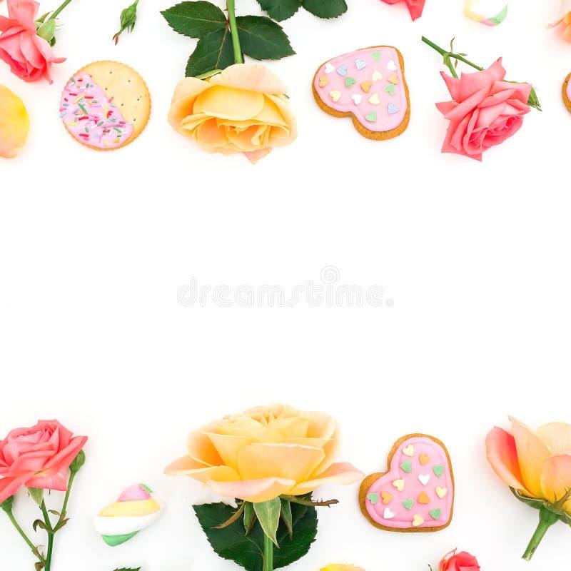 Capítulo hecho de las flores de las rosas con las galletas y la melcocha en el fondo blanco imagen de archivo libre de regalías