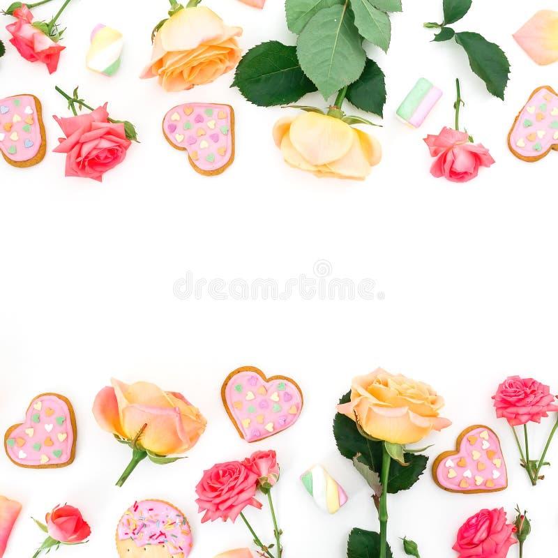 Capítulo hecho de las flores y de los pétalos de las rosas con las galletas y la melcocha en el fondo blanco Endecha plana imagen de archivo libre de regalías