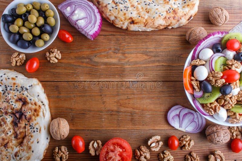 Capítulo hecho de los tomates, del queso de la mozzarella, de aceitunas, de kiwi, y de las nueces en fondo de madera marrón imagenes de archivo