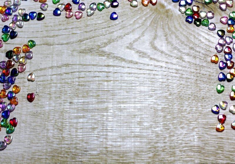 Capítulo la frontera de los corazones coloridos de las cuentas de cristal en fondo de madera imagen de archivo libre de regalías