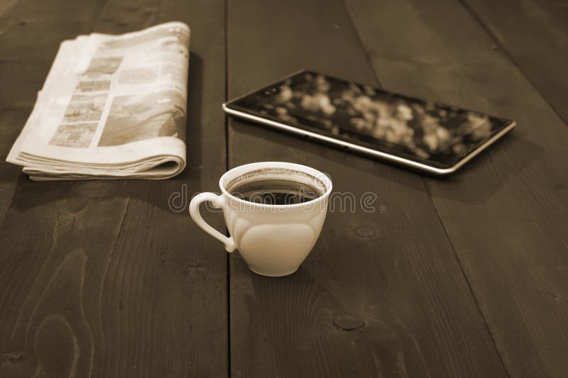 A cap of coffee newspaper and tablet - sepia color royalty free stock photos