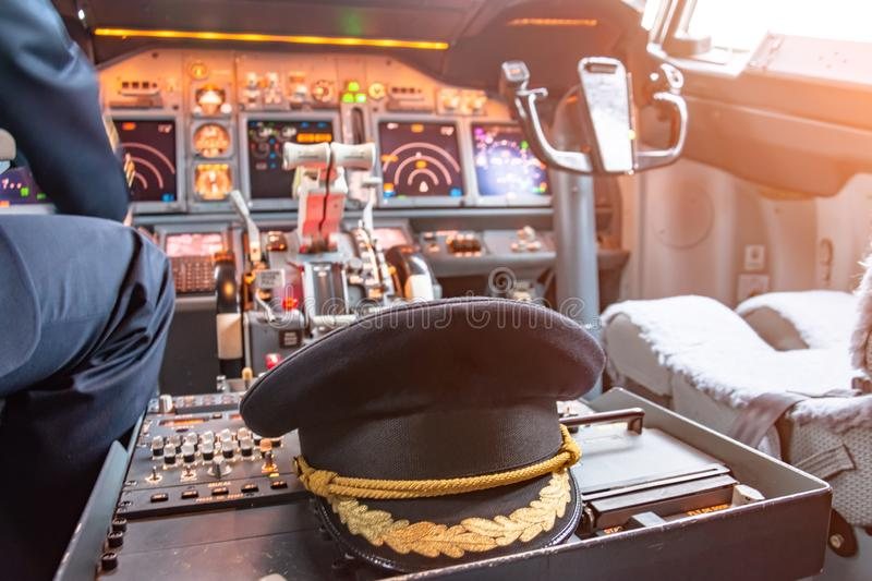 Cap of the commander of the aircraft in the cockpit. Civil Aviation Concept royalty free stock image