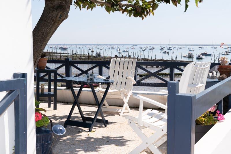 Cap Ferret France海滩村Le Canon海滨椅和木桌的露台 库存照片