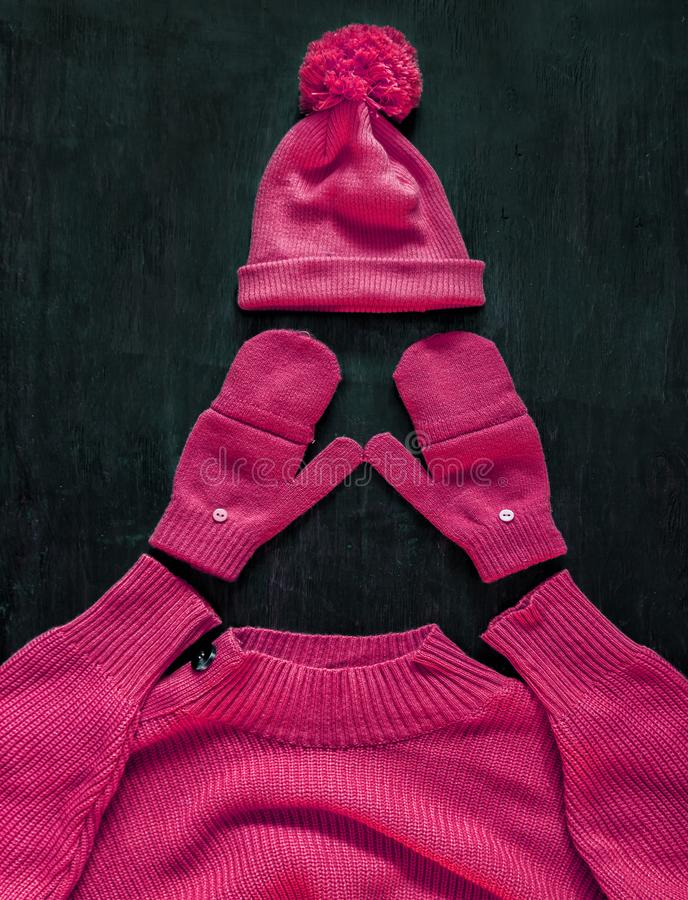 Cap with pompon, mittens, sweater in pink-red-manzhent-purple color on a dark wooden background. Top view, flat lay.Concept stock image