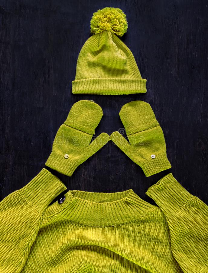 Cap with pompon, mittens, sweater in yellow-green color on a dark wooden background. Top view, flat lay.Concept stylish youth warm stock photography