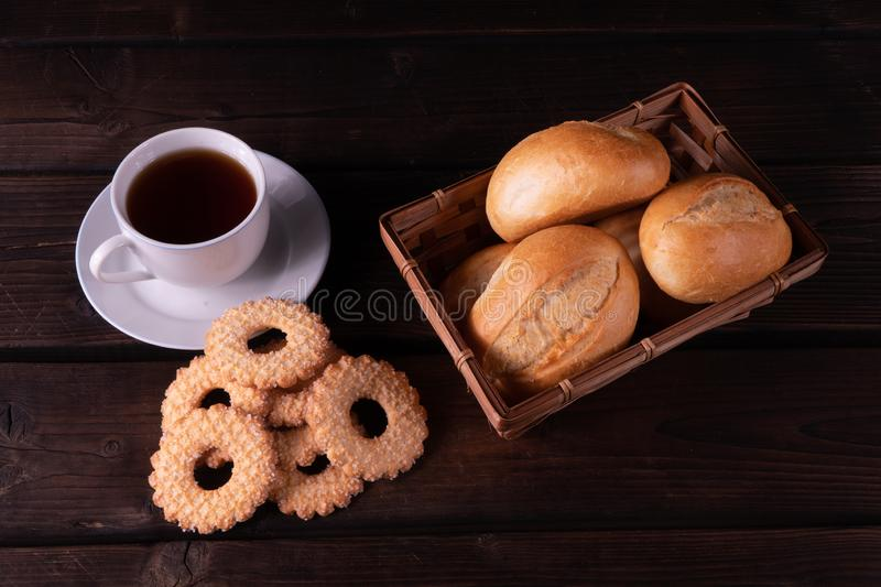 Cap of tea, home made cookies and buns in bread basket on a wooden background, low key, rustic royalty free stock photography