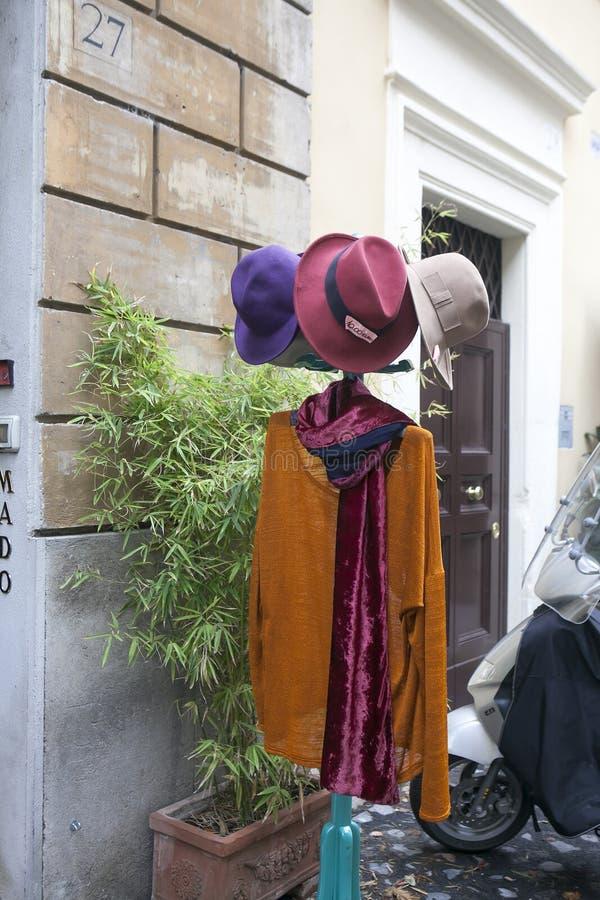 Capa de Brown y sombreros coloreados en una suspensión para la venta en la entrada a la tienda imágenes de archivo libres de regalías