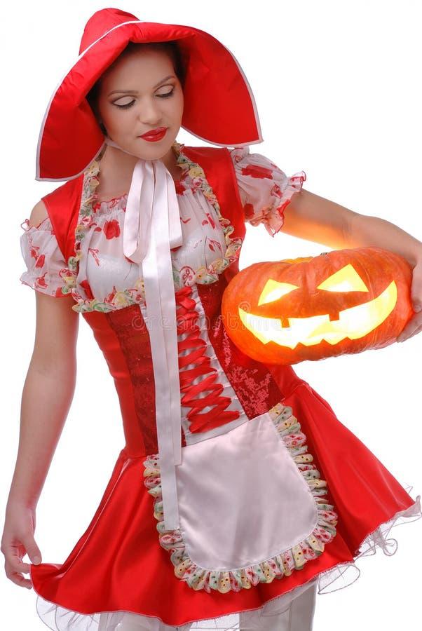 A capa de equitação vermelha pequena com abóbora de Halloween imagem de stock royalty free
