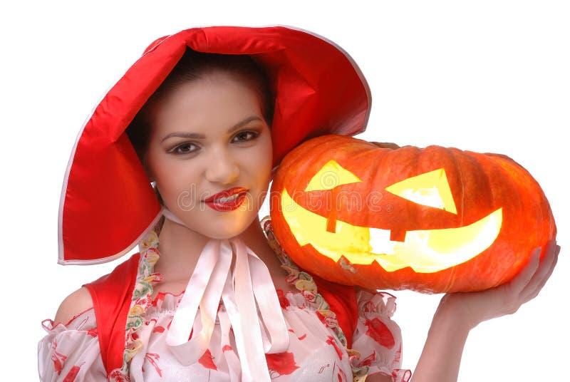 A capa de equitação vermelha pequena com abóbora de Halloween imagem de stock