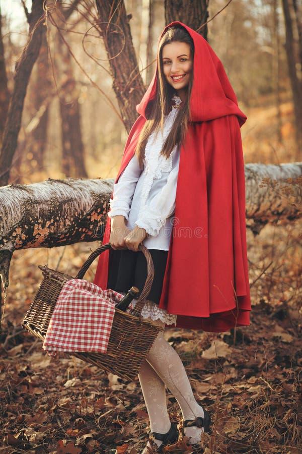 A capa de equitação vermelha pequena feliz levanta na floresta imagens de stock royalty free