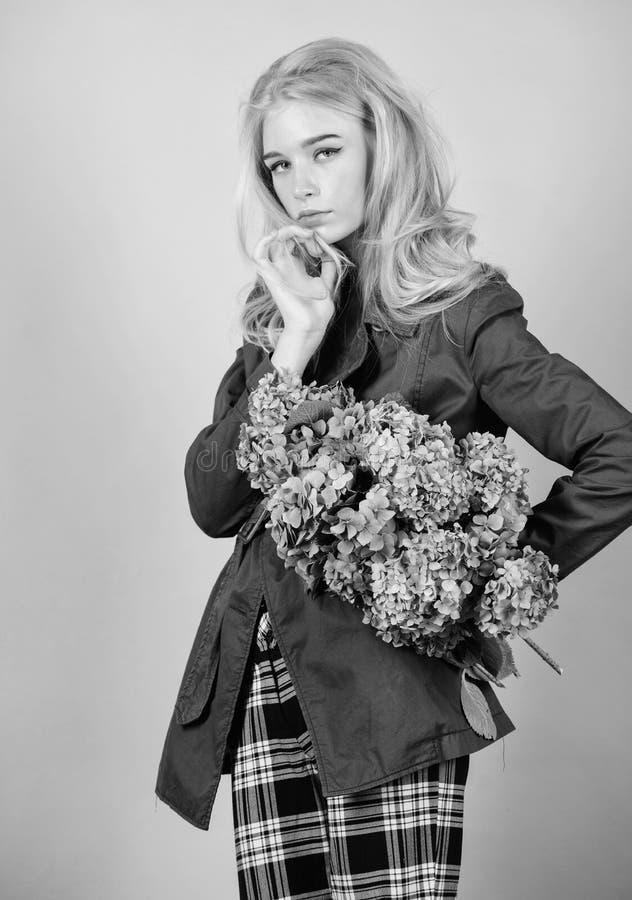 Capa de moda Debe tener concepto Ropa y accesorio Pelo rubio de la mujer que presenta la capa con el ramo de las flores Chica imagen de archivo