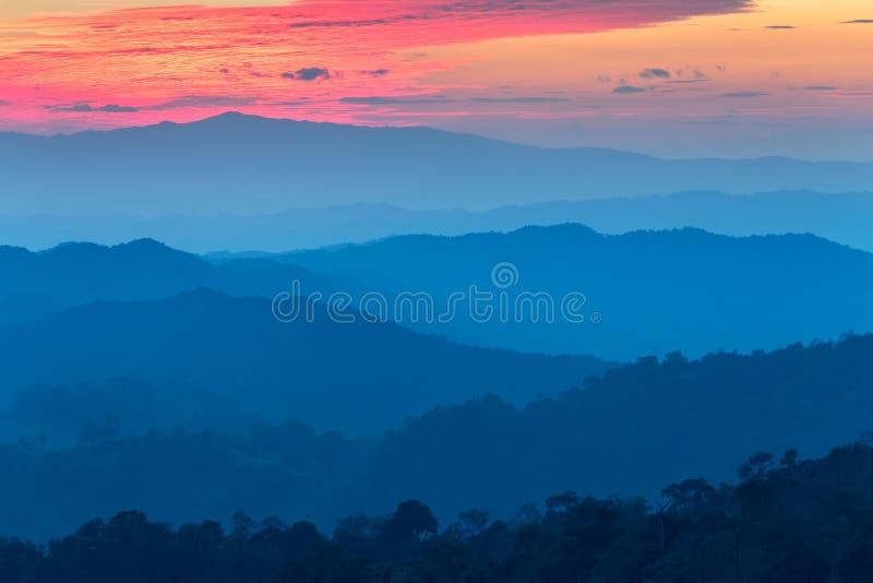 Capa de montañas en la niebla en el tiempo de la puesta del sol con el cielo ardiente, fotografía de archivo