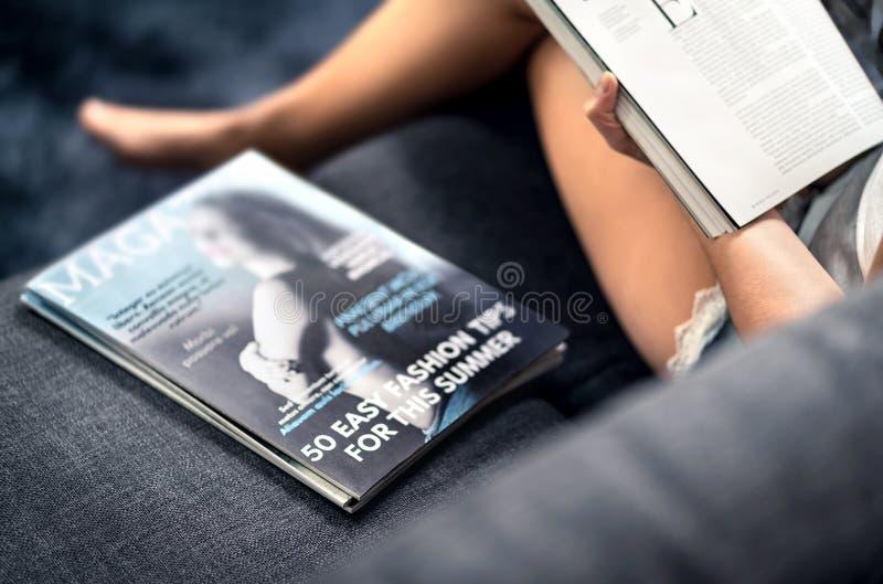 Capa de revista com o texto e títulos no sofá Forma da leitura da mulher e artigo da beleza sobre as tendências as mais atrasadas imagem de stock royalty free